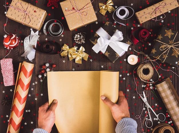 Homem, mão, desdobramento, rolo, de, embrulhando, papel kraft, para, embalagem, natal, caixa presente Foto gratuita