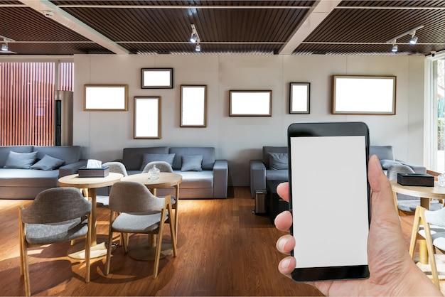 Homem, mãos, segurando, em branco, tela, um, smartphone, e, obscurecido, sala de estar, fundo Foto Premium