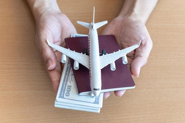 Homem mãos segurando notas de 100 dólares e avião na mesa de madeira. conceito de viagens Foto Premium