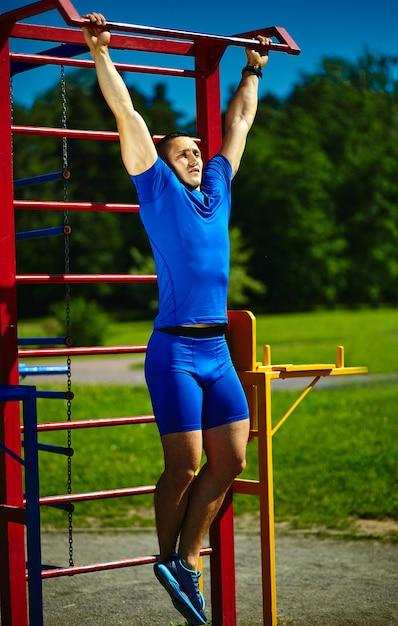 Homem masculino saudável saudável considerável do atleta do srtong que exercita no parque da cidade - conceitos da aptidão em um lindo dia de verão na barra horizontal Foto gratuita