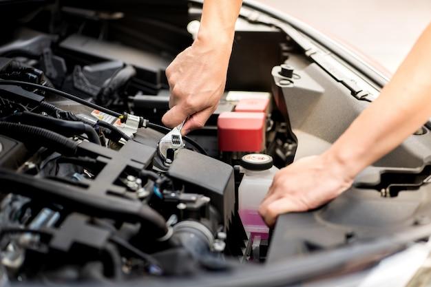 Homem mecânico trabalhando e reparando o motor do carro no centro de serviço do carro. detalhes de peças de automóvel automóvel metal motor. do motor do veículo moderno, indústria, mecânico e negócios. Foto Premium