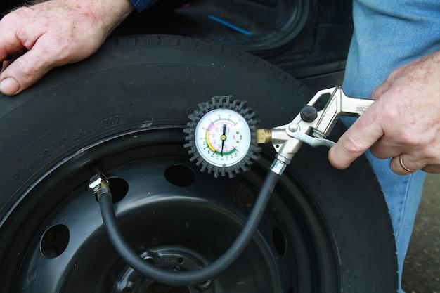 Homem, medindo a pressão dos pneus Foto Premium
