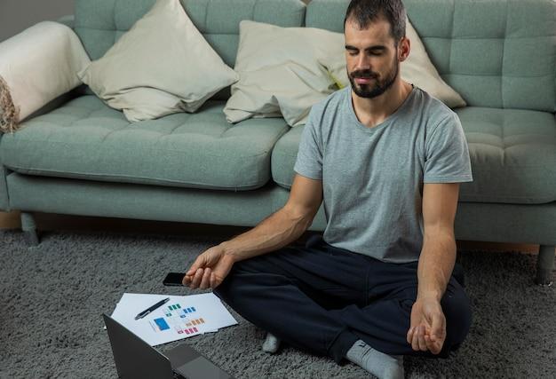 Homem meditando ao lado do sofá antes de começar a trabalhar Foto gratuita