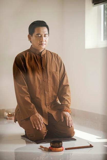 Homem meditando com tigela de canto e incenso Foto gratuita