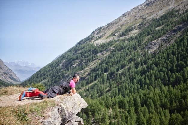 Homem, mentindo, ligado, precipício, olhar, paisagem montanhosa Foto Premium