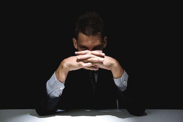 Homem misterioso com as mãos entrelaçadas, olhando da sombra escura Foto Premium