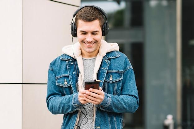 Homem moderno com fones de ouvido em ambiente urbano Foto gratuita