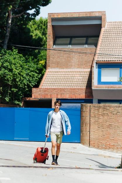 Homem moderno com saco de bagagem andando na rua Foto gratuita