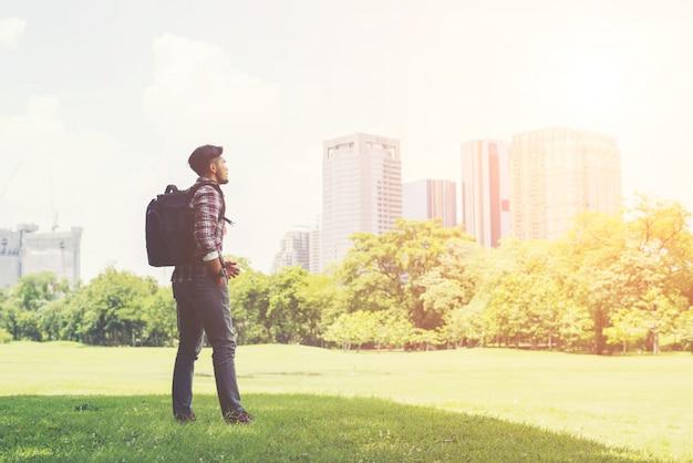 Homem moderno jovens apreciar a vista da cidade do parque, antes de ir para tr Foto gratuita
