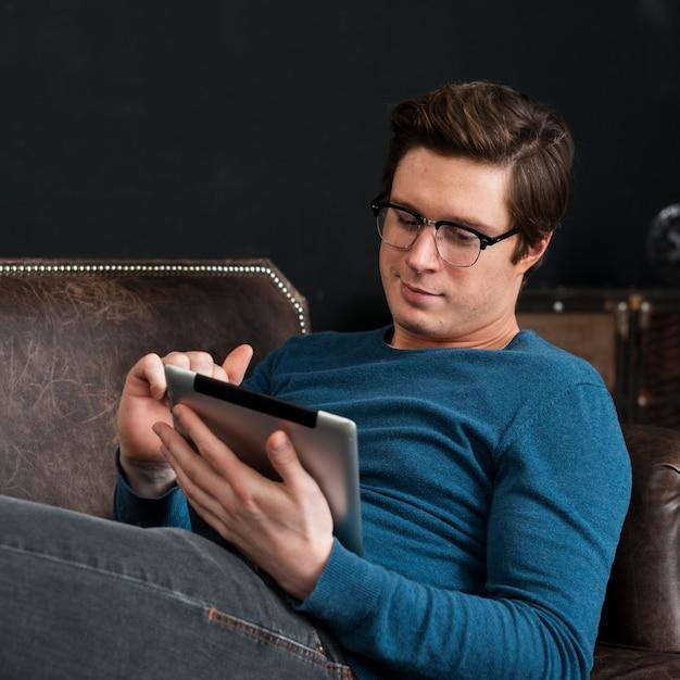 Homem moderno olhando em seu tablet enquanto fica no sofá Foto gratuita