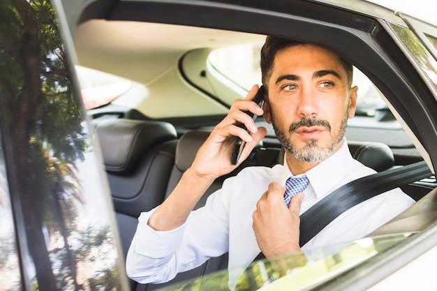 Homem moderno, sentado no carro, ajustando a gravata do pescoço, falando no celular Foto gratuita