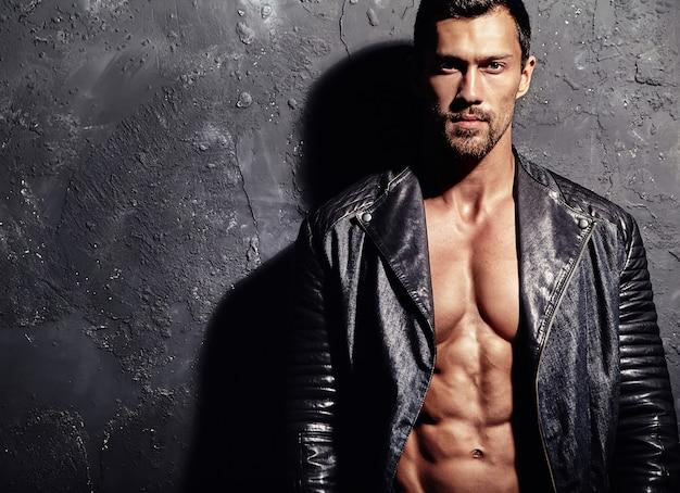 Homem molhado bonito no fundo da parede preta Foto gratuita