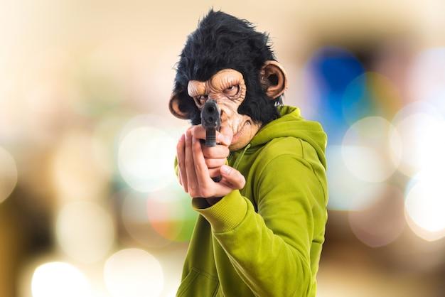 Homem monkey que dispara com uma pistola no fundo desenfocado Foto Premium