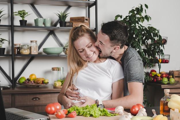 Homem, morder, bochechas mulher, estar, atrás de, a, contador cozinha, com, legumes Foto gratuita
