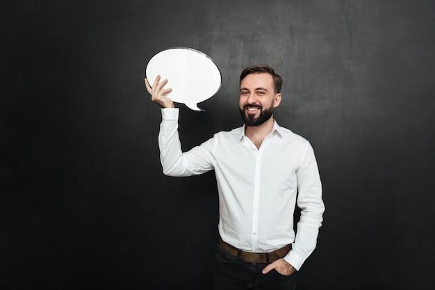 Homem morena bonita segurando o balão em branco e olhando para a câmera sobre o espaço da cópia de parede cinza escuro Foto gratuita