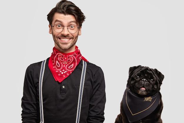 Homem moreno estiloso com lenço vermelho ao lado do cachorro Foto gratuita