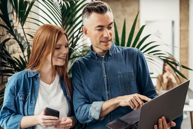 Homem mostrando algo em um laptop para seu colega de trabalho Foto gratuita