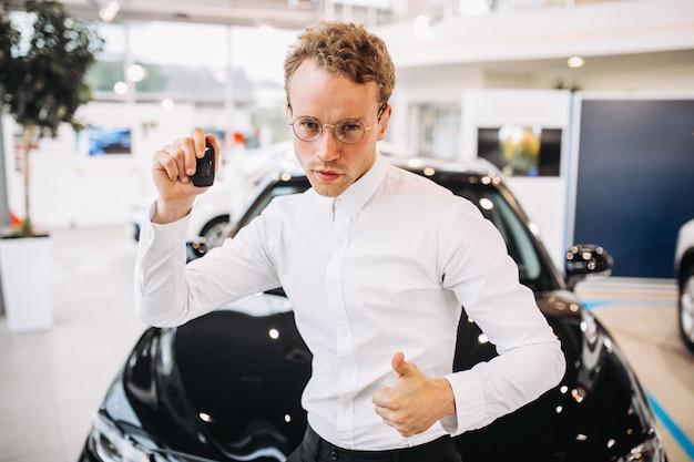 Homem, mostrando, polegares cima, frente, um carro, em, um, showroom carro Foto gratuita