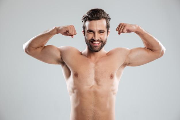 Homem mostrando seu bíceps e olhando para a câmera Foto gratuita