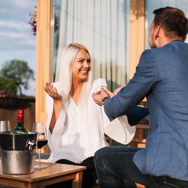 Homem, mostrando, um, anel acoplamento, para, seu, feliz, namorada, em, um, restaurante Foto gratuita