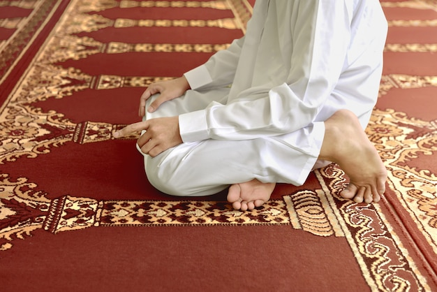 Homem muçulmano ajoelhado enquanto rezava a deus Foto Premium