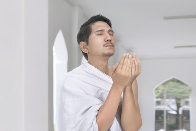 Homem muçulmano asiático religioso com pano hajj rezar Foto Premium