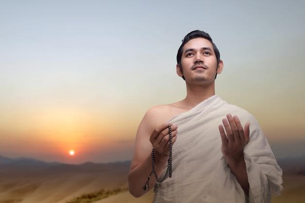 Homem muçulmano em roupas ihram rezando com contas de oração nas mãos Foto Premium