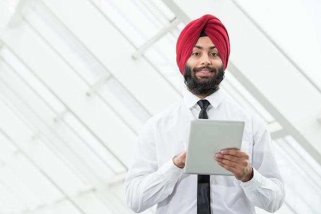 Homem muçulmano fica com um tablet e olha para algo. Foto Premium