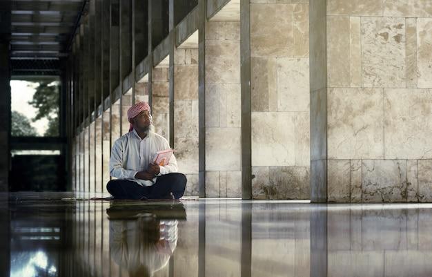 Homem muçulmano religioso lendo o alcorão sagrado Foto Premium