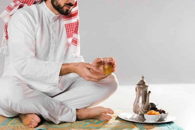 Homem muçulmano segurando uma xícara pequena de chá tradicional Foto gratuita