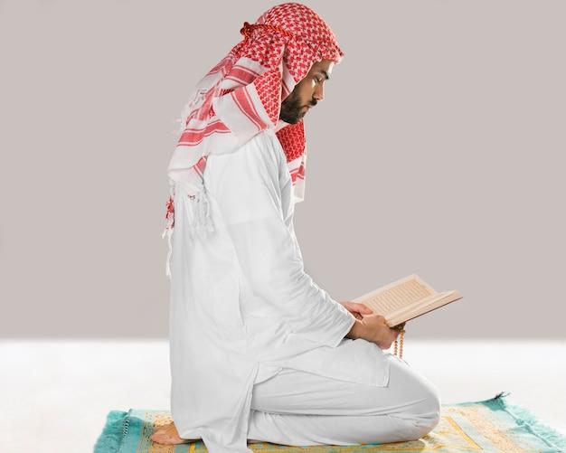 Homem muçulmano sentado e lendo do alcorão Foto gratuita