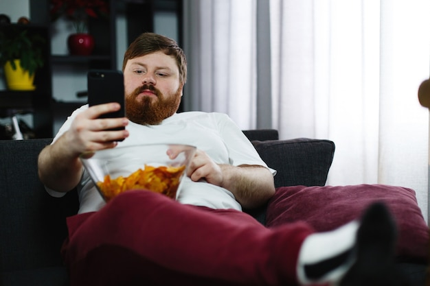 Homem muito gordo sorri verificando seu smartphone enquanto ele se senta no sofá e come Foto gratuita