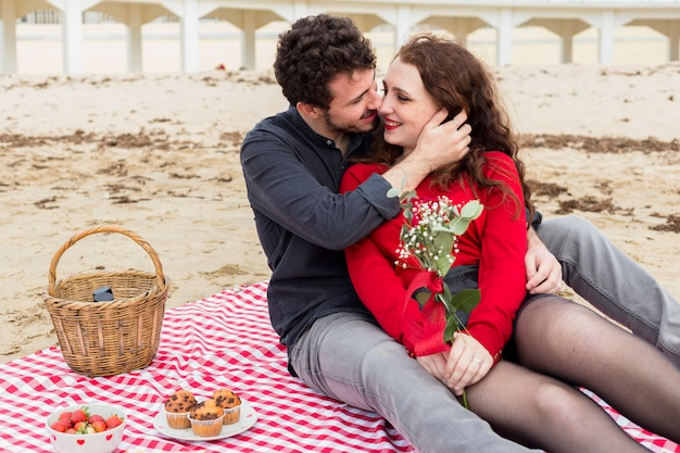 Homem, mulher abraçando, com, flores, ligado, coverlet Foto gratuita