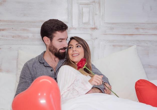 Homem, mulher abraçando, com, rosa, cama Foto gratuita