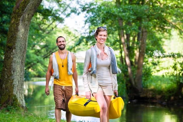 Homem mulher, carregar, canoa, para, floresta, rio Foto Premium