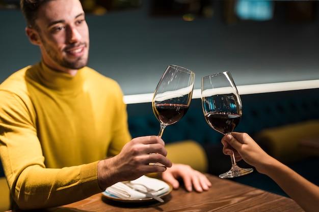 Homem mulher, clanging, copos vinho, em, tabela, em, restaurante Foto gratuita