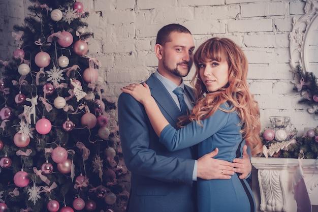 Homem mulher, em, sala, com, árvore natal, e, lareira Foto Premium