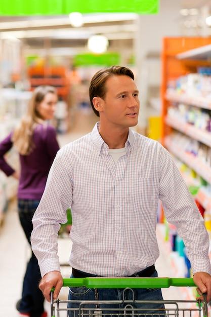 Homem mulher, em, supermercado, com, carro shopping Foto Premium