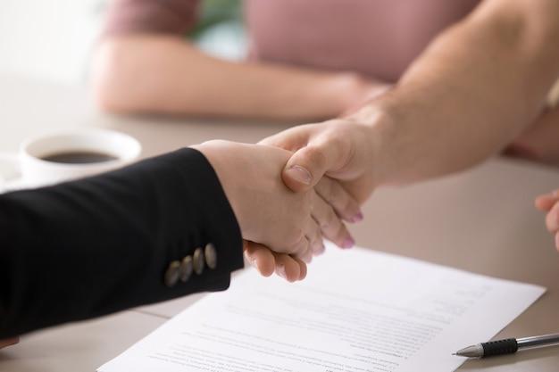 Homem mulher, handshaking, após, assinar documentos, sucesso, negócio, closeup Foto gratuita