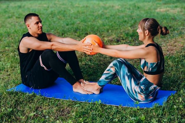Homem mulher, junto, fazendo, exercício, com, um, bola, ao ar livre Foto Premium