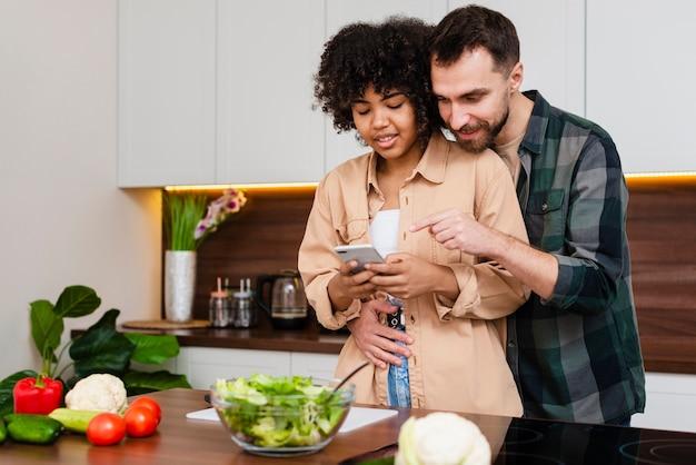 Homem mulher, olhando telefone, cozinha Foto gratuita