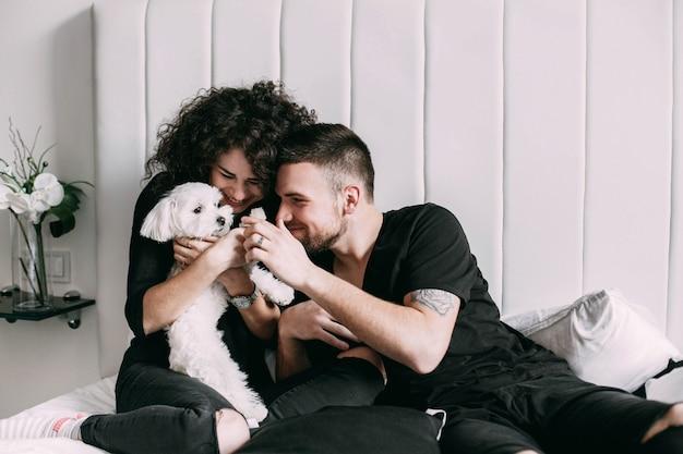 Homem, mulher, pretas, jogo, pequeno, branca, cão, cama Foto gratuita
