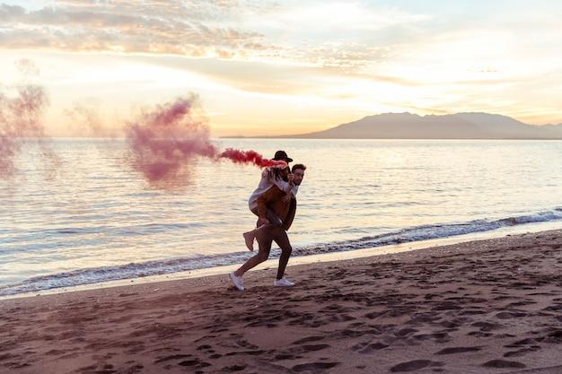Homem, mulher segura, com, bomba fumaça, ligado, costas, ligado, costa mar Foto gratuita