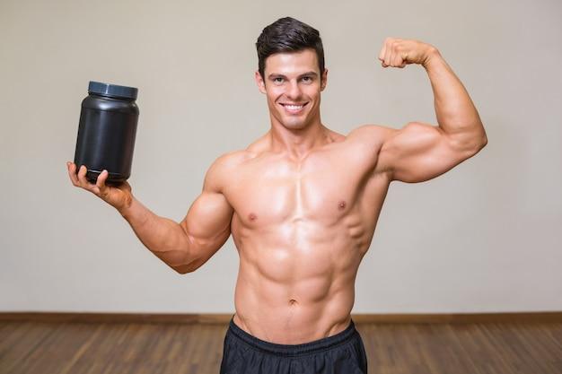 Homem muscular posando com suplemento nutricional na academia Foto Premium