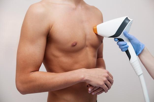Homem musculoso atleta com pele clara suave. depilação e depilação de cabelos em salão de beleza. conceito de depilação a laser masculino. esteticista, usando aparelhos modernos para procedimentos. cuidados com a pele e beleza Foto Premium