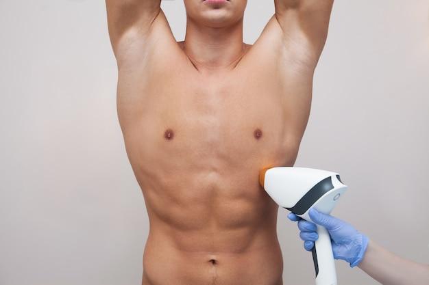 Homem musculoso atleta segurando seus braços e mostrando axilas, axilas, pele clara e macia. depilação e depilação de cabelos em salão de beleza. conceito de depilação a laser masculino Foto Premium