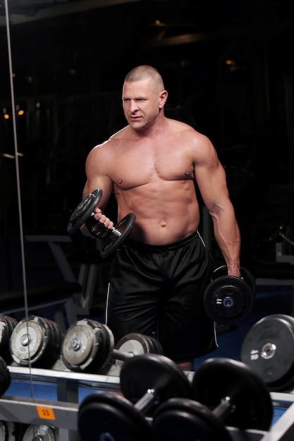 Homem musculoso bonito em uma academia Foto gratuita
