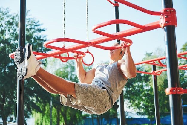 Homem musculoso com lindo torso se exercitando nas barras horizontais Foto gratuita