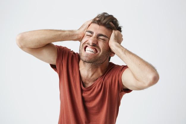 Homem musculoso com raiva emocional, vestindo camiseta vermelha, fechando os olhos com força e gritando de dor ou total descrença, mantendo as mãos na cabeça. emoções e sentimentos humanos negativos Foto gratuita