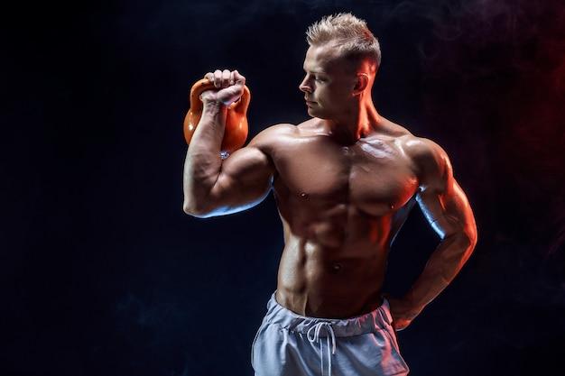 Homem musculoso concentrado fazendo exercício com kettlebell Foto Premium